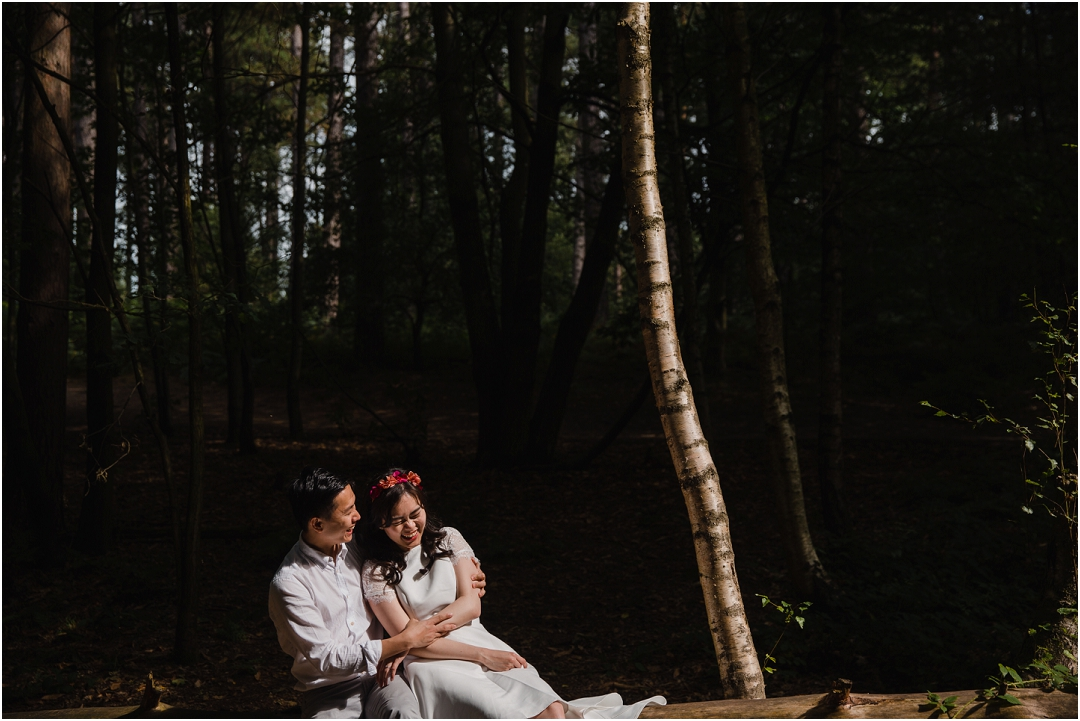 couple in patch of forest light on their engagement shoot